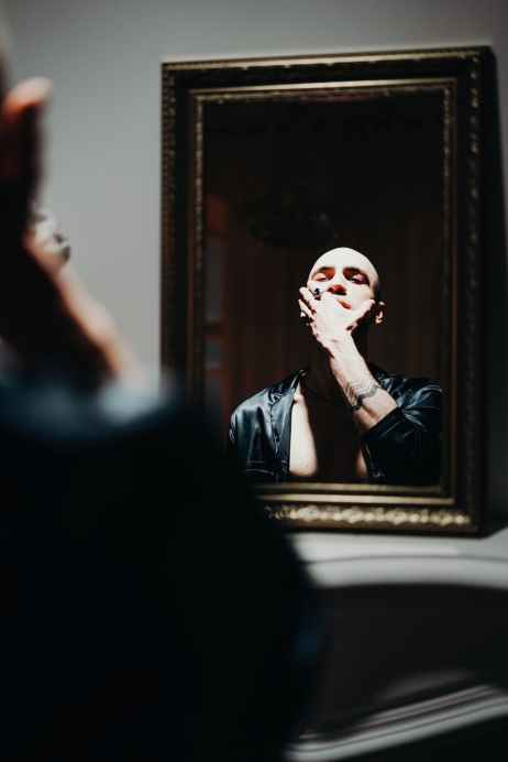 man looking at the mirror in holding his face